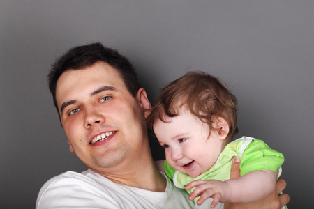 green clothes: Young happy father holds his little son in green clothes in grey studio Stock Photo