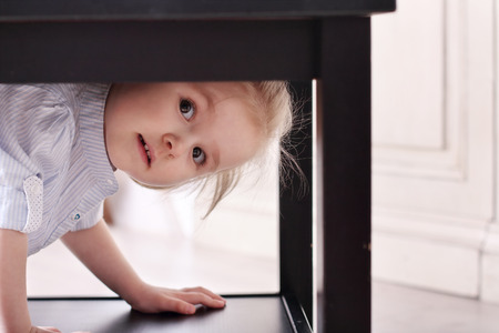 climbed: Cute little blond girl in striped shirt climbed in recess table