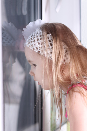 white bandage: Closeup of cute little blond girl with white bandage looking out window