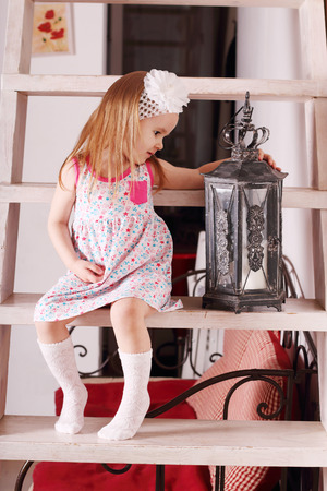 luminaire: Little cute blond girl in dress sitting on wooden stairs with with old luminaire. Focus on lamp