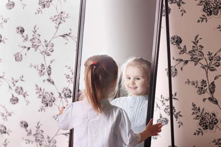 Little cute blond girl in striped shirt looking at his reflection in mirror Standard-Bild