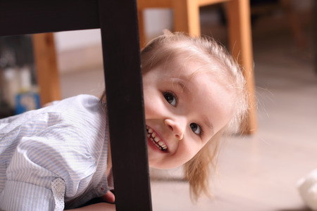 laughing: Cute little blond girl laughing peeking out from behind table leg