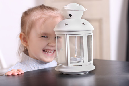 luminaire: Cute little blond girl laughing before luminaire with candle. Focus on lamp Stock Photo