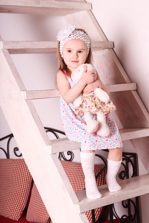 Little cute blond girl in dress sitting on wooden stairs with soft toy in her hands Stock Photo