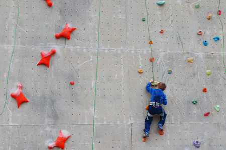 climbing wall: Back of boy climbing with rope on special wall for climbing outdoor Stock Photo