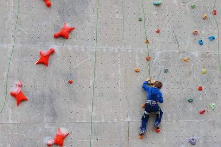 niño escalando: Parte posterior del niño de subir con la cuerda en especial de la pared para escalar al aire libre