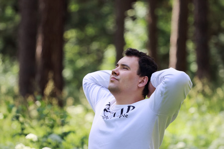 tcp ip: Young handsome man in white looks up and rests in summer sunny forest Stock Photo