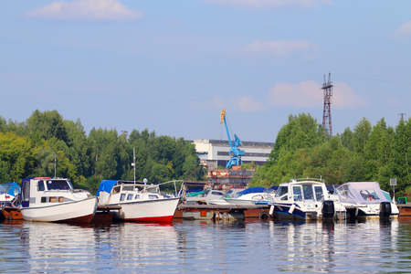 motorboats: Many small modern motorboats at pier on river at summer sunny day Stock Photo