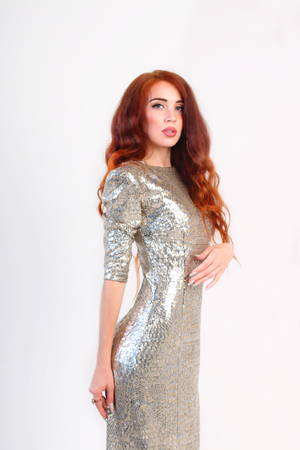 silver dress: Beautiful girl with red hair and shiny silver dress standing