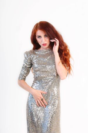 silver dress: Beautiful young girl with red hair and shiny silver dress standing Stock Photo