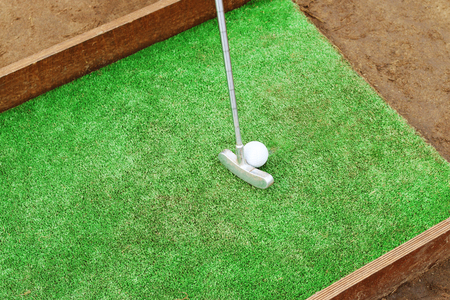 factitious: Artificial lawn, putter and golf ball on wooden stand for training