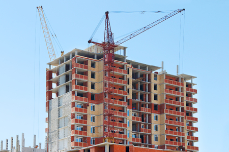 urban apartment: Two tall cranes and brick building under construction at sunny day