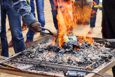 tongs: Burning coals with bright orange flame and hand of blacksmith with tongs Stock Photo