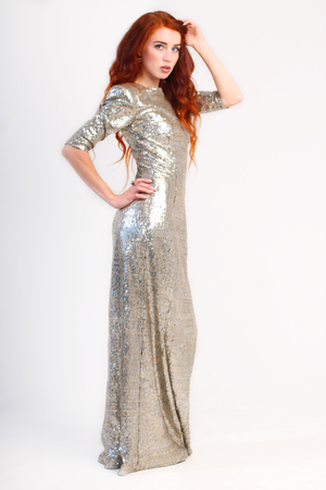 silver dress: Beautiful girl with red hair and shiny silver dress in studio. Full body view