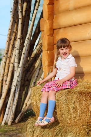 skirts: Bastante feliz niña se sienta en el heno amarillo cerca de la pared de la casa de madera en el pueblo Foto de archivo