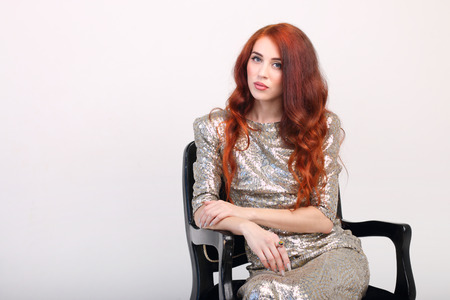 sits on a chair: Beautiful girl with red hair and dress sits on black wooden chair