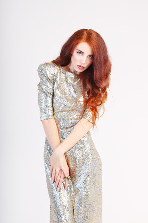 silver dress: Beautiful young girl with red hair and shiny silver dress standing with hands on hips