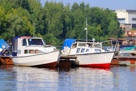 motorboats: Small modern motorboats at pier on river at summer sunny day