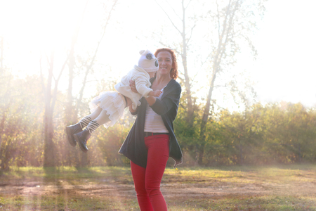 daugther: Happy young mother plays with her little daugther at sunny autumn day