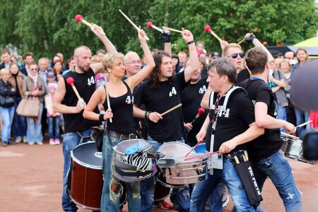 synchronously: PERM, RUSSIA - JUN 15, 2014: Group of drummers 44 Drums perform at open air festival White Nights
