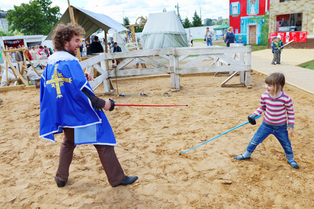 mosquetero: PERM, RUSSIA, JUN 18, 2014: Little girl learns fencing (girl witn model release) with young man at open air festival White Nights Editorial