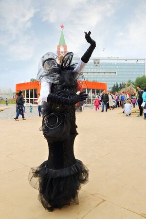 nights: PERM, RUSSIA - JUN 15, 2014: Woman in black costume poses during street theaters show at open air festival White Nights