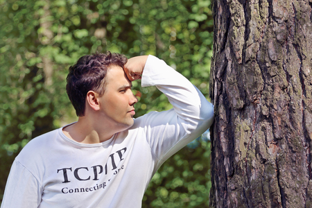 face in tree bark: Young handsome man in white leans his elbow on tree and thinks in summer sunny forest Stock Photo