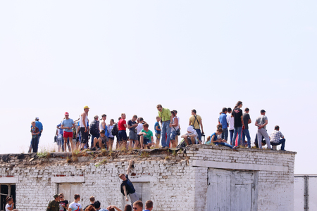 spectators: PERM, RUSSIA - JUN 27, 2015: Spectators on roof on airshow Wings of Parma