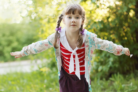 depicts: Pretty smiling little girl with braids depicts bird at summer sunny day
