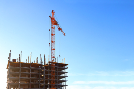 hoist: Bright stationary hoist and building under construction at sunny winter day Stock Photo
