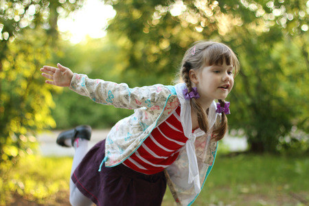 depicts: Beautiful little girl with braids depicts bird at sunny day. Shallow dof