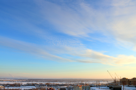 wintering: Frozen river and panoramic view, roof of tall building and sky at cold winter evening