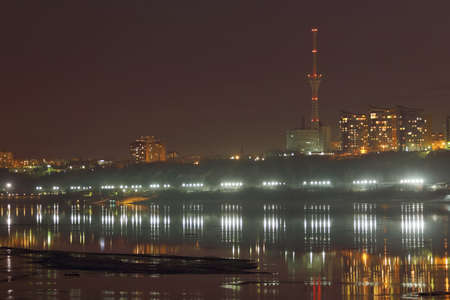 glory of the snow: Embankment, buildings and tv tower with illumination and reflection in river at winter night Stock Photo