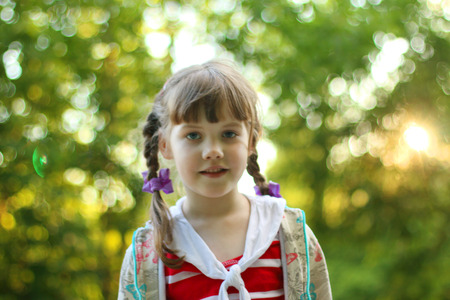 dof: Portrait of pretty smiling little girl with braids outdoor. Shallow dof