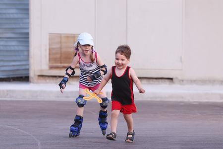 niño en patines: pequeños patines niña feliz en el asfalto y el muchacho con carreras de boomerang en noche de verano