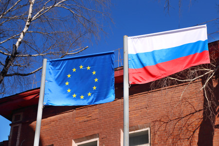 enmity: Flags of Russia and European Union waving in wind on street