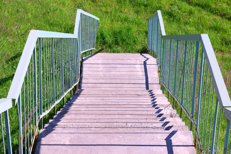 concrete steps: Concrete steps, metal blue railing and green grass at summer day