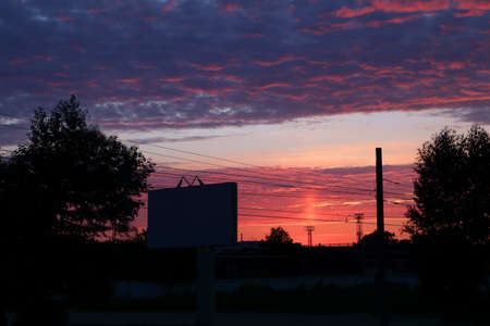 vermeil: Beautiful sky during red sunset, clouds and silhouettes of trees, billboard and wires
