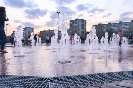 perm: Dry fountain in town in spring evening, people walk, Close up of water jet