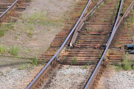 turnout: Close up view of railway with wooden sleepers, grass and turnout