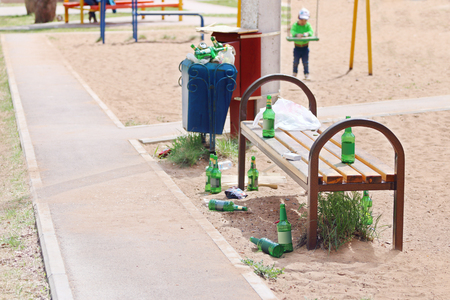 near beer: Many beer bottles near bench on children playground at summer day Stock Photo