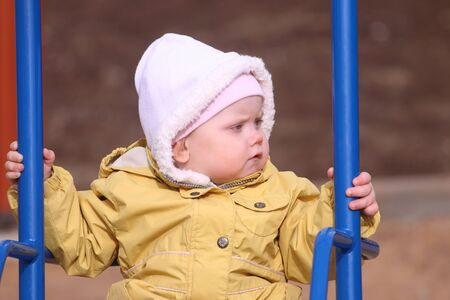 yellow jacket: Little cute girl in yellow jacket swings on playground at sunny spring day