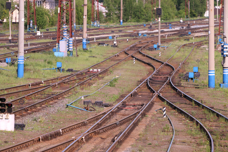 turnouts: Railways with wooden sleepers, poles, grass and turnouts at summer day