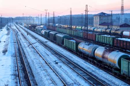freightliner: Freight train with tanks moves on railways at snowy winter evening Stock Photo