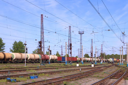 freightliner: Freight train with tanks moves on rusty railway at sunny summer day Stock Photo