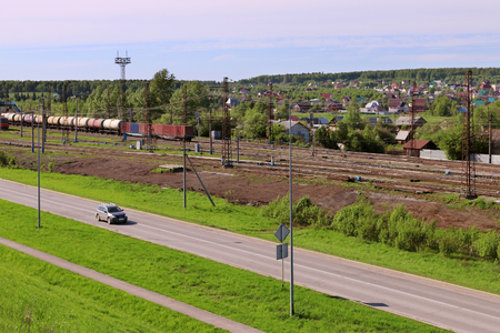 freight train: Freight train with tanks stand on railway station and car moves on asphalt road