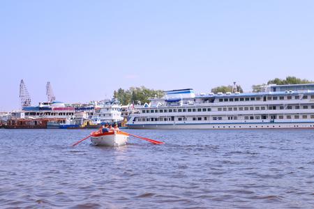 passenger ships: Boat with oars floating on river against background of large passenger ships