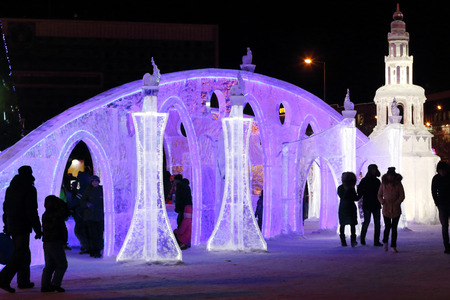 PERM, RUSSIA - JAN 4, 2016: People walk in illuminated Ice town, Ice town in Perm - traditional winter attraction