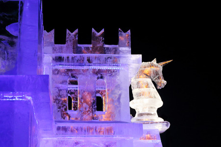PERM, RUSSIA - JAN 4, 2016: Illuminated unicorn on wall in Ice town, Ice town in Perm - traditional winter attraction