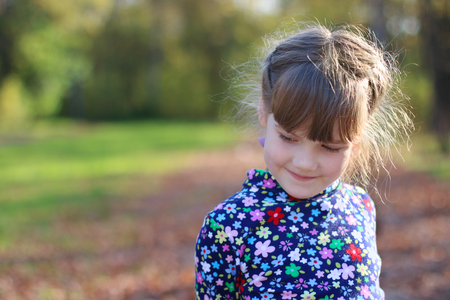Cute little girl smiles and looks away in sunny green park, shallow dof, close up